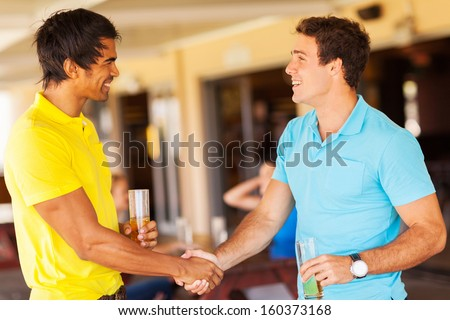 happy friends handshaking at the party - stock photo