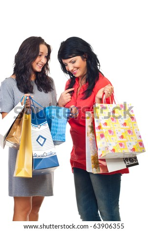 Happy friends having conversation at shopping and one looking in a bag to see what her friend bought isolated on white background - stock photo