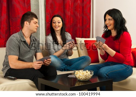 Happy friends having fun and playing cards game together - stock photo