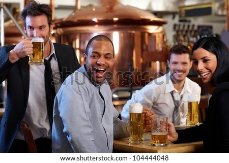 Happy friends having fun in pub watching sport in TV together drinking beer cheering for team. - stock photo