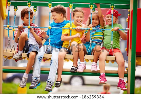 Happy friends having fun on swing on playground - stock photo