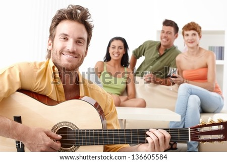 Happy friends having fun together, playing guitar, smiling.