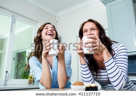 Happy friends holding coffee mugs at table in kitchen - stock photo