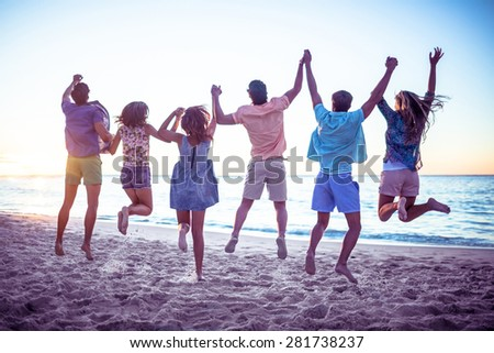 Happy friends holding hands and jumping at the beach