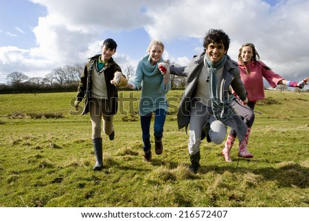 Happy friends holding hands and running in sunny, rural field