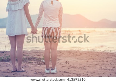 Happy Friends holding hands in nature, encouraging concept.