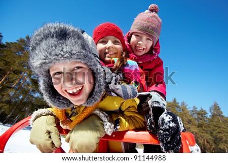 Happy friends in winterwear tobogganing in park - stock photo