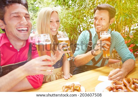 Happy friends laughing in beer garden in Bavaria in summer - stock photo