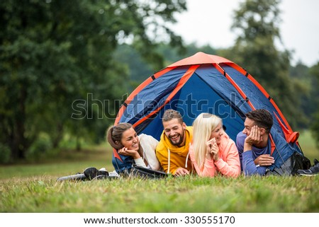 Happy friends lying in their tent in the countryside - stock photo