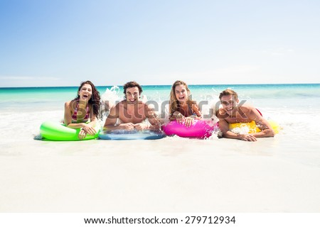 Happy friends lying on inflatable mattress above the water at the beach - stock photo