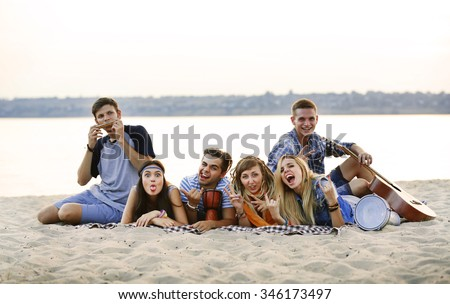 Happy friends lying on the beach