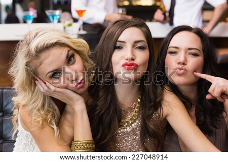 Happy friends making silly faces at the bar - stock photo