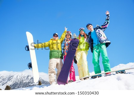 Happy friends men and women stand in snow with snowboards lifting and waving hands - stock photo