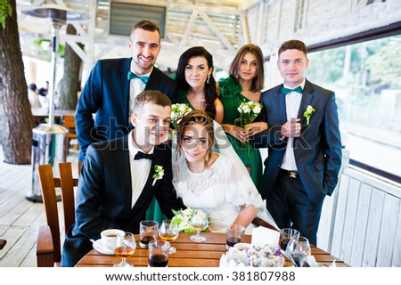 Happy friends of wedding couple and groomsman with bridesmaids at cafe