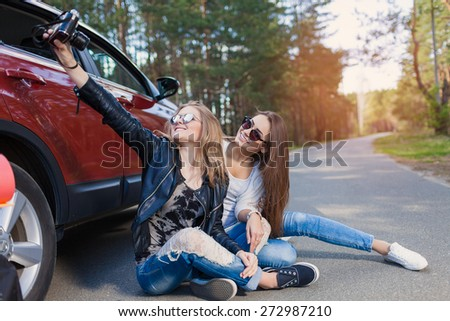 Happy friends on road trip taking selfie on a summers day. Little holiday trip - stock photo