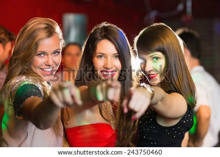 Happy friends pointing at camera at the nightclub