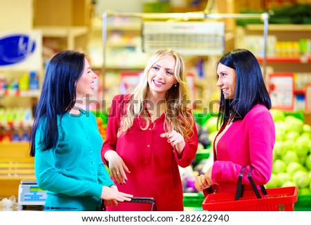 happy friends shopping together in grocery supermarket - stock photo