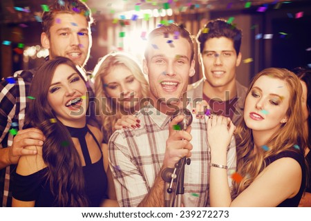 Happy friends singing karaoke together against flying colours