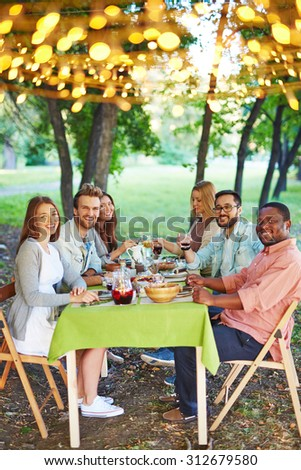 Happy friends sitting by Thanksgiving table and looking at camera outdoors - stock photo
