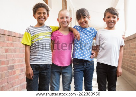 Happy friends smiling at camera at elementary school - stock photo