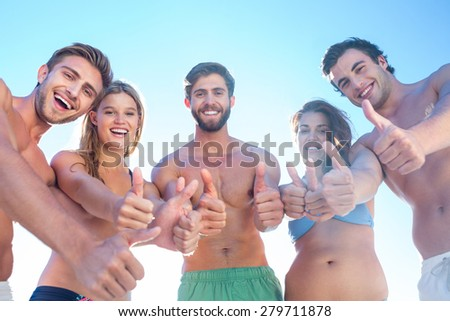 Happy friends smiling at camera showing thumbs up at the beach - stock photo