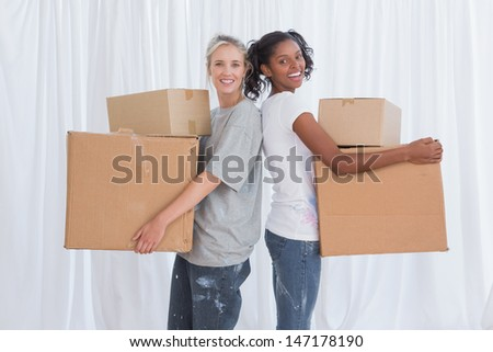 Happy friends standing back to back holding moving boxes looking at camera - stock photo
