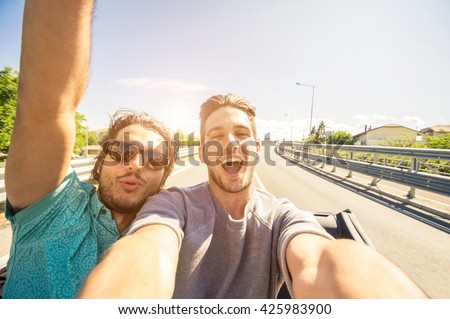 Happy friends taking a selfie at car trip - Two caucasian tourist travelling around the world - stock photo