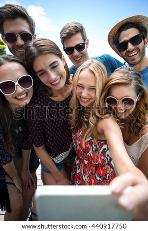 Happy friends taking a selfie near swimming pool on a sunny day - stock photo