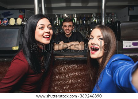 Happy friends taking selfie with Bartender - stock photo