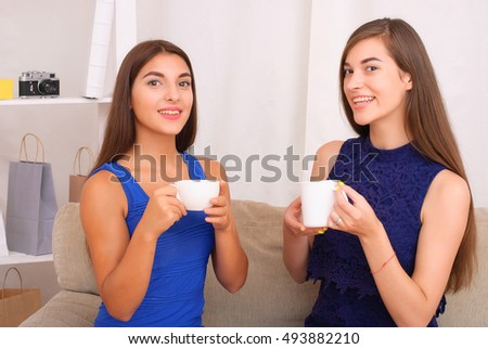 happy friends talking and drinking coffee and tea sitting on a couch at home