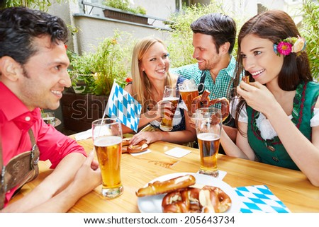 Happy friends talking and flirting in beer garden in summer - stock photo