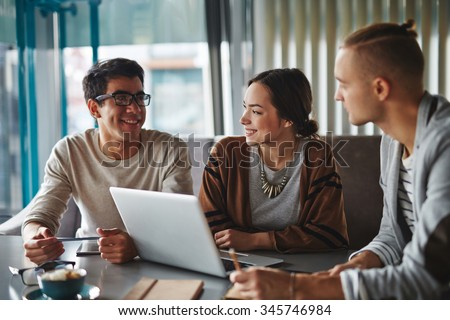 Happy friends talking in cafe - stock photo