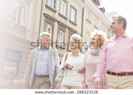 Happy friends talking while walking in city - stock photo