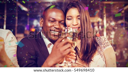 Happy friends toasting with champagne against flying colours
