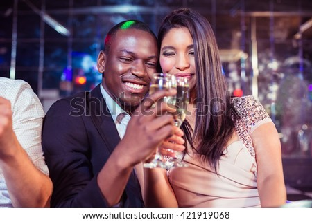 Happy friends toasting with champagne in the night club