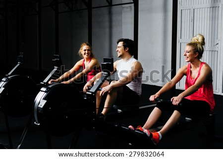 Happy friends training on rowing machine - stock photo