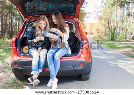 Happy friends traveling on a red car. Holiday trip of friends - stock photo