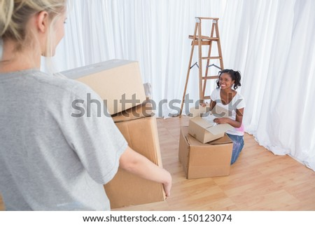 Happy friends unpacking moving boxes in their new home - stock photo