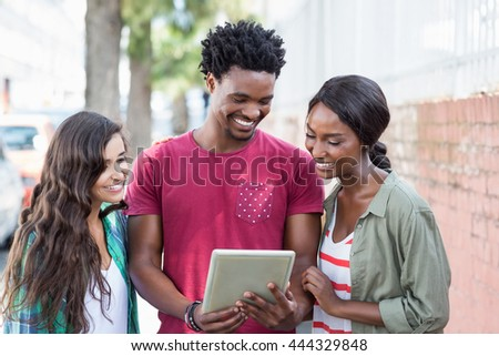 Happy friends using digital tablet outdoors - stock photo
