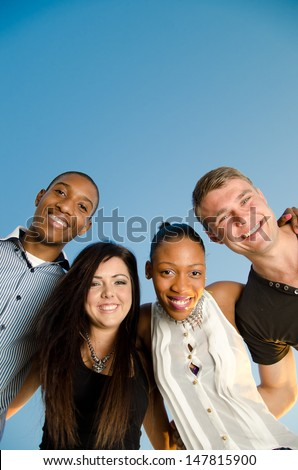 Happy Friends version holding each other against a clear blue sky (potential copy space) - stock photo