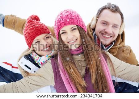 Happy friends walking in winter - stock photo
