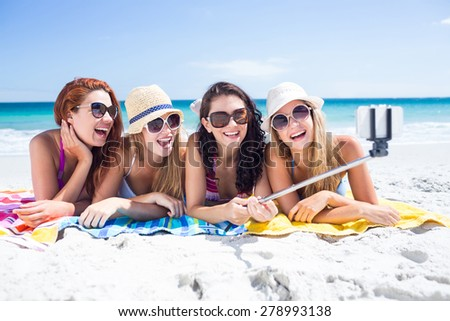 Happy friends wearing sun glasses and taking selfie at the beach - stock photo