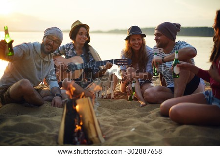 Happy friends with drinks and guitar sitting by campfire - stock photo