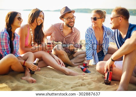 Happy friends with drinks sitting on sand by water