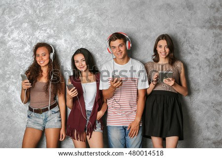 Happy friends with gadgets on grey background