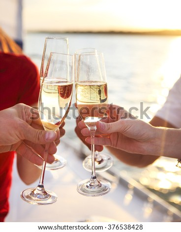 Happy friends with glasses of champagne on yacht. Vacation, travel, sea and friendship concept. Closeup. - stock photo