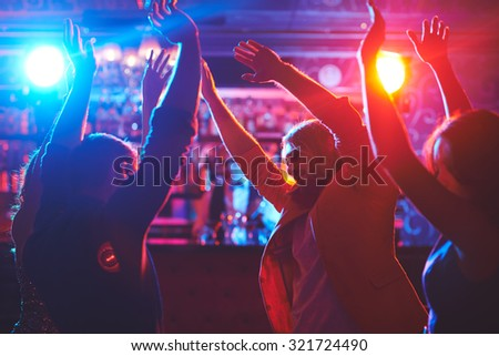 Happy friends with raised arms dancing at night club - stock photo