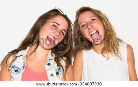 Happy friends with their skateboards taking out their tongues