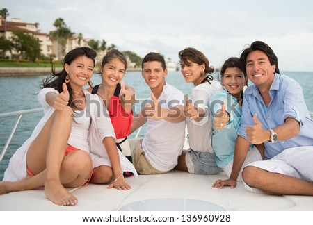 Happy friends with thumbs up in a yacht enjoying the summer - stock photo