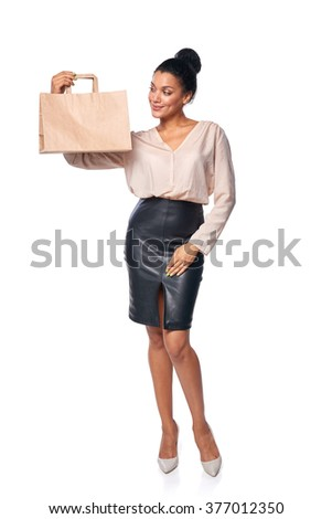 Happy full length woman holding a paper shopping bag with blank copy space, over white background - stock photo
